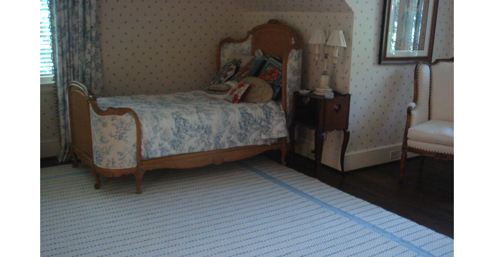 Montagne Handwoven handmade white and blue texture rug on display in guest room