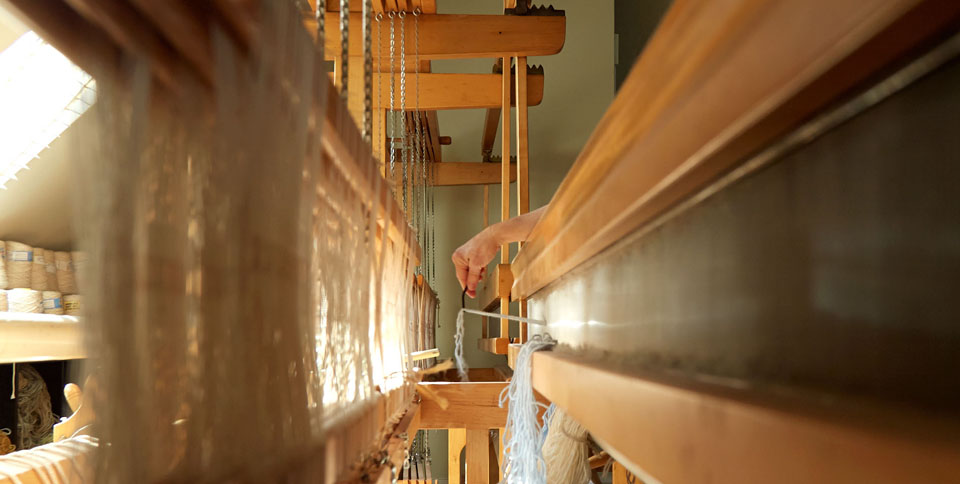 At the Montagne Handwoven Atlanta design studio, a hand reaches over the reed to warp the loom by hand